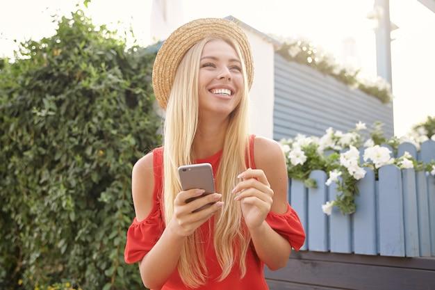 Mulher jovem e atraente feliz com a cabeça branca com maquiagem natural, mantendo o smartphone nas mãos levantadas enquanto sorri alegremente, e está de bom humor enquanto caminha ao ar livre