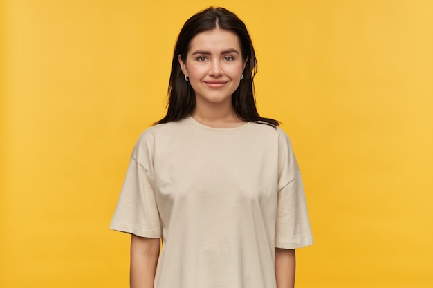 Mulher jovem e atraente feliz com cabelo escuro e camiseta branca em pé, sorrindo sobre a parede amarela