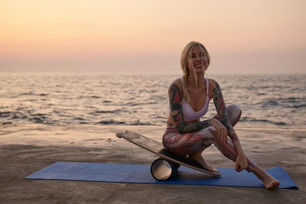 Mulher jovem e atraente feliz com cabelo loiro praticando esportes à beira-mar durante o nascer do sol, posando com vista para o mar, vestindo roupas esportivas, apoiando-se na prancha de equilíbrio e olhando alegremente