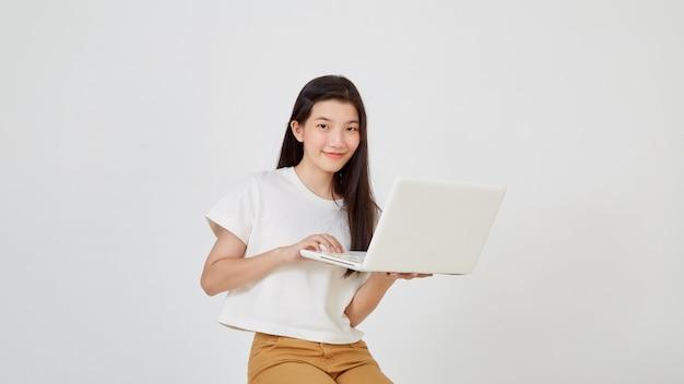 Mulher jovem e atraente feliz com um laptop sentado de pernas cruzadas olhando para o espaço vazio no fundo branco do estúdio