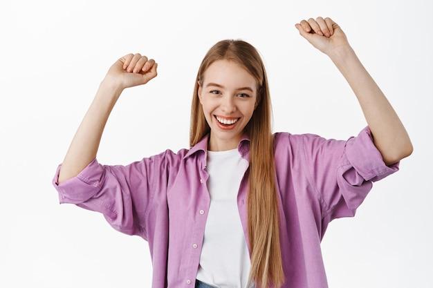 Mulher jovem e atraente feliz dançando, comemorando e festejando, se divertindo, sorrindo na frente, levantando as mãos despreocupada, em pé sobre uma parede branca