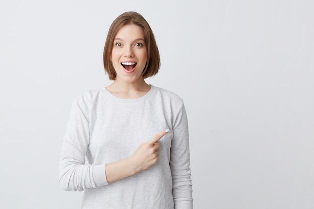 Mulher jovem e atraente feliz de manga comprida em pé e apontando para o lado isolado