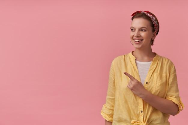 Mulher jovem e atraente feliz em uma camisa amarela com bandana na cabeça olhando e apontando para o lado na copyspace sobre a parede rosa