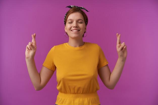 Mulher jovem e atraente feliz em uma camiseta amarela com fita na cabeça e olhos fechados mantém os dedos cruzados e fazendo um pedido sobre a parede roxa