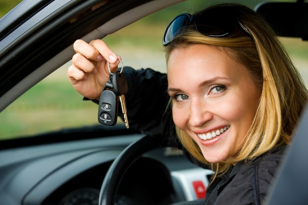 Mulher jovem e atraente feliz mostra as chaves do carro novo - ao ar livre