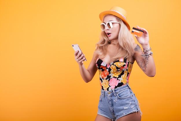 Mulher jovem e atraente feliz segurando e mostrando o cartão de crédito no estúdio sobre fundo amarelo