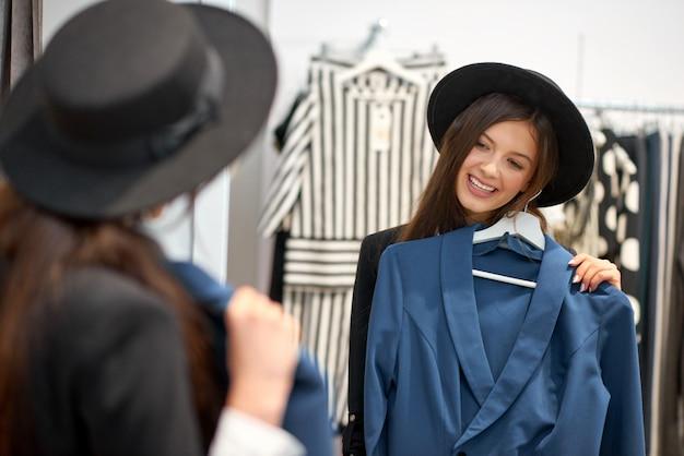 Mulher jovem e atraente feliz sorrindo com alegria enquanto experimentava roupas novas na loja de moda posando em frente ao espelho copyspace estilo de vida pessoas positividade bem-estar consumismo conceito.