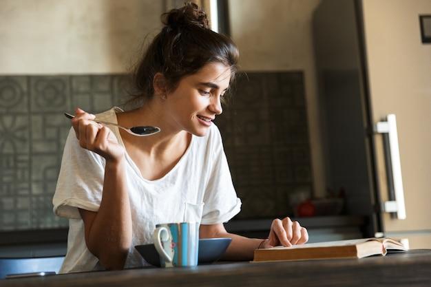 Mulher jovem e atraente feliz tomando café da manhã saudável na cozinha de casa, lendo um livro
