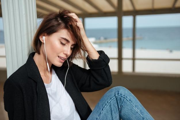 Mulher jovem e atraente feliz usando fones de ouvido, sentado e relaxando em um caramanchão à beira-mar