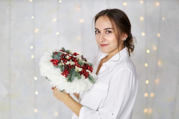 Mulher jovem e atraente fica com um buquê original nas mãos de uma parede de luz