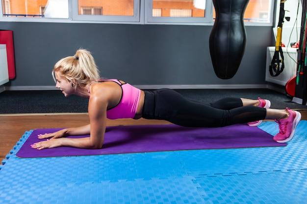 Mulher jovem e atraente fitness exercitando resistência praticando exercícios de prancha na aula de fitness