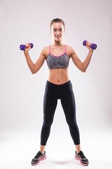 Mulher jovem e atraente fitness fazendo exercícios aeróbicos diferentes com halteres em branco vestida com roupas esportivas