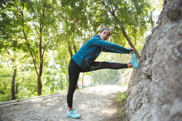 Mulher jovem e atraente fitness vestindo roupas esportivas, fazendo exercícios ao ar livre, fazendo exercícios de alongamento