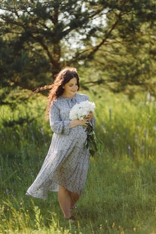 Mulher jovem e atraente grávida lá fora