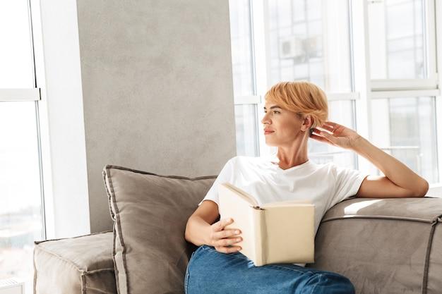 Mulher jovem e atraente lendo um livro enquanto está sentado em um sofá em casa