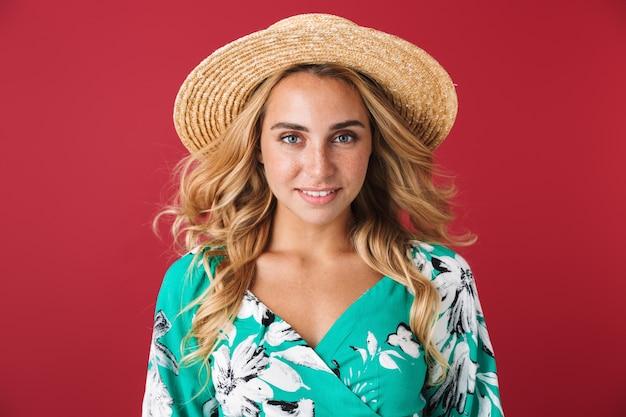 Mulher jovem e atraente loira com vestido de verão e chapéu de palha em pé isolado na parede rosa, olhando para a câmera