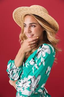Mulher jovem e atraente loira com vestido de verão e chapéu de palha em pé isolado na parede rosa, posando