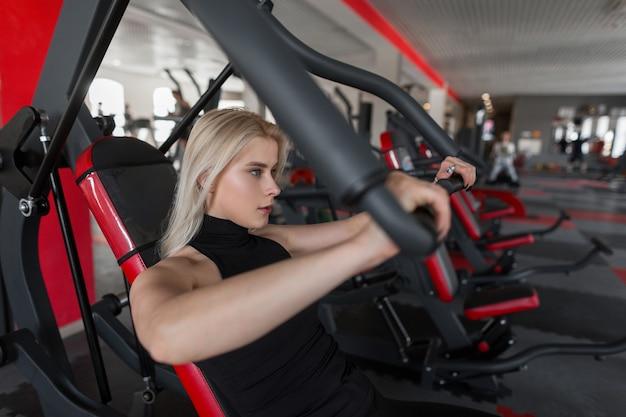 Mulher jovem e atraente loira em roupa esportiva preta treinando na academia