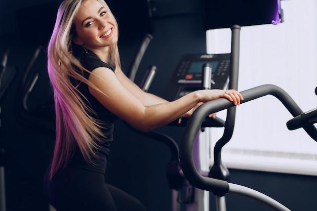 Mulher jovem e atraente loira se exercitando em um aparelho de treinamento cardiovascular