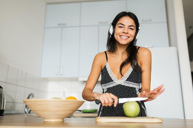 Mulher jovem e atraente, magra e sorridente, se divertindo cozinhando na cozinha pela manhã, tomando café da manhã, vestida com roupa de pijama, ouvindo música em fones de ouvido, cortando maçã, estilo de vida saudável