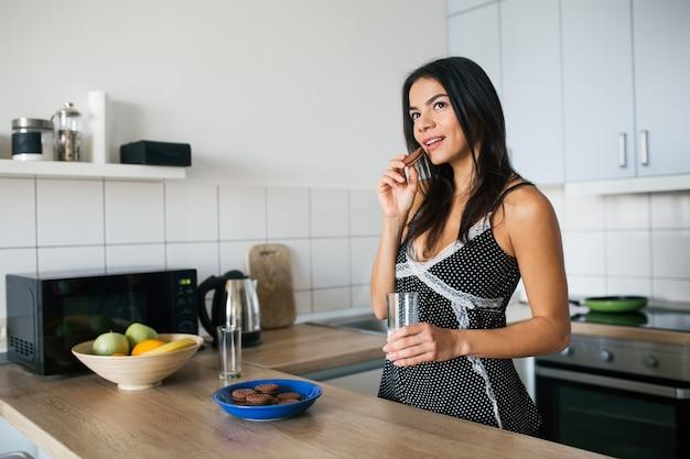 Mulher jovem e atraente, magra, sorridente, se divertindo na cozinha pela manhã, tomando café da manhã, vestida com roupa de pijama, comendo biscoitos bebendo leite