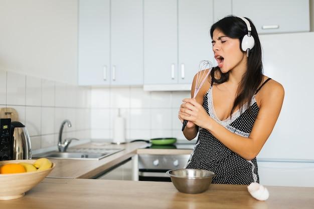 Mulher jovem e atraente, magrinha, sorridente, se divertindo cozinhando ovos na cozinha pela manhã, tomando café da manhã, vestida com roupa de pijama, ouvindo música em fones de ouvido cantando