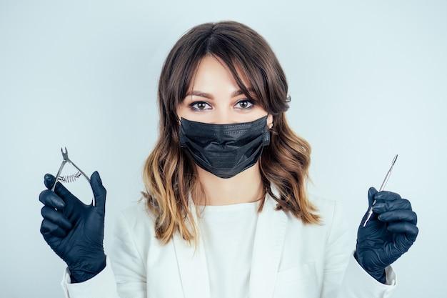 Mulher jovem e atraente manicure profissional (mestre em manicure) em um casaco branco, máscara e luvas de borracha preta segura ferramentas para remover cutículas e uma lixa de unha em um salão de beleza