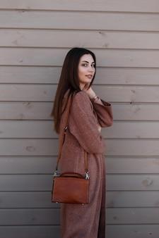 Mulher jovem e atraente moderna com cabelo bonito num casaco de primavera longa juventude com bolsa na moda de couro fica perto de uma parede vintage de madeira na cidade. linda garota com sorriso atraente, posando ao ar livre.