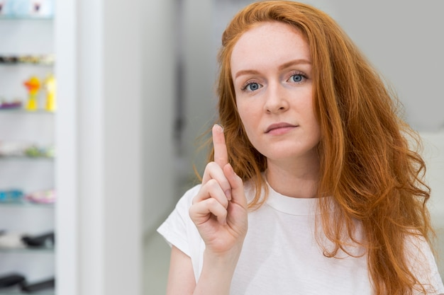 Mulher jovem e atraente moderna mostrando a lente de contato e olhando para a câmera