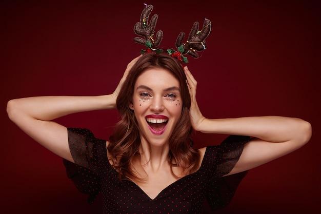 Mulher jovem e atraente morena alegre, de mãos dadas na cabeça dela e olhando feliz, preparando-se para a celebração do natal e usando o aro de holday, isolado