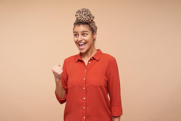 Mulher jovem e atraente morena cheia de alegria com maquiagem natural, levantando alegremente a mão enquanto se alegra com algo, de pé sobre uma parede bege