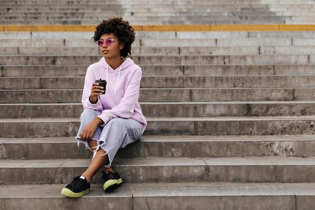 Mulher jovem e atraente morena de jeans, moletom com capuz e óculos de sol rosa segura a xícara de café e se senta na escada do lado de fora