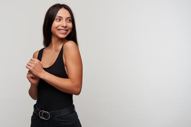 Mulher jovem e atraente morena feliz com penteado casual olhando alegremente para o lado e cruzando as mãos levantadas, sorrindo amplamente enquanto posam