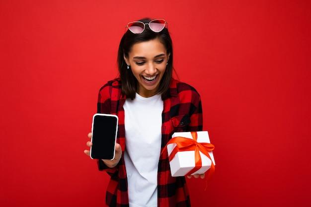 Mulher jovem e atraente morena feliz isolada sobre uma parede de fundo vermelho usando uma camiseta casual branca