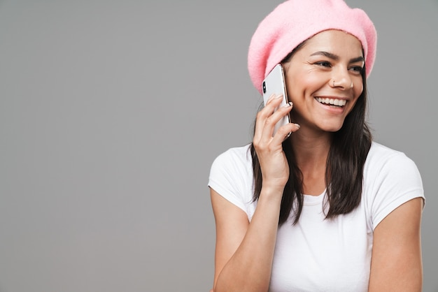 Mulher jovem e atraente morena feliz usando uma boina em pé, isolada na parede cinza, falando no celular