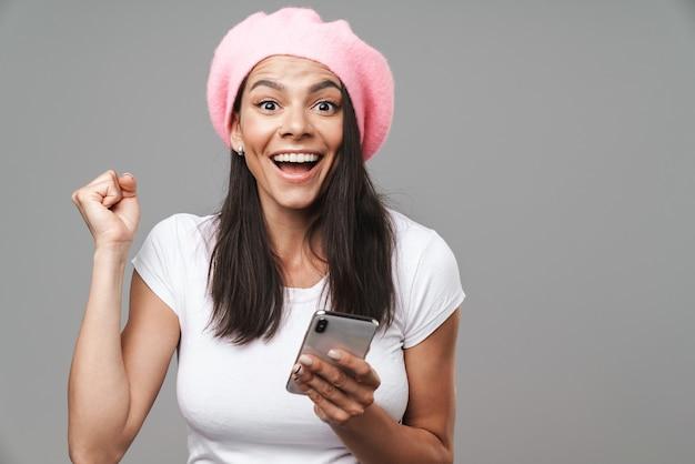 Mulher jovem e atraente morena feliz usando uma boina em pé, isolada na parede cinza, segurando um telefone celular, comemorando o sucesso