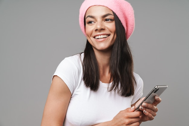 Mulher jovem e atraente morena feliz usando uma boina em pé, isolada sobre uma parede cinza, segurando um telefone celular