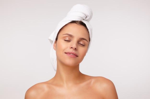 Mulher jovem e atraente morena satisfeita, mantendo os olhos fechados enquanto aproveita o tempo após o banho e sorrindo positivamente, em pé contra um fundo branco