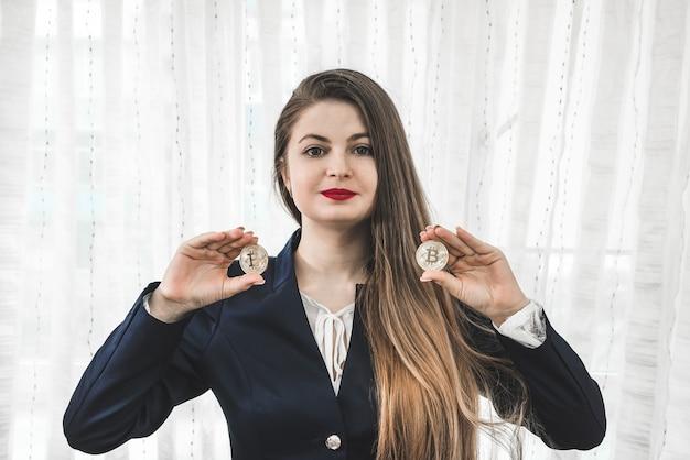 Mulher jovem e atraente mostrando bitcoins dourados, criptomoeda