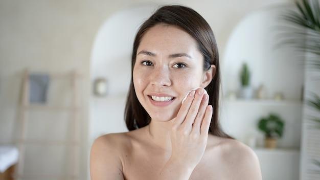 Mulher jovem e atraente multiétnica após o banho, limpando a pele e os poros, a almofada de algodão usa gel de limpeza bifásico, removendo a maquiagem e a sujeira, desfrute de um tratamento de beleza eficaz.