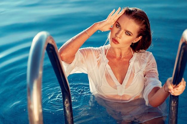 Mulher jovem e atraente na camisa branca molhada em uma piscina