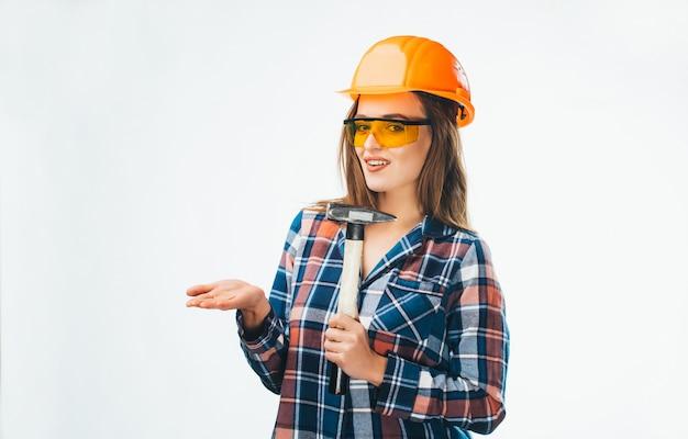 Mulher jovem e atraente na construção de capacete com martelo e óculos de proteção laranja com branco
