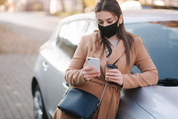 Mulher jovem e atraente na máscara protetora com uma xícara de café fica perto do carro e usa o telefone.