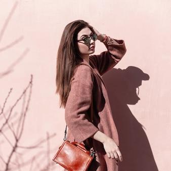 Mulher jovem e atraente na moda com cabelo comprido bonito com lábios sensuais em óculos de sol da moda com bolsa posando em pé no sol perto de parede rosa vintage na cidade. modelo de menina doce elegante em roupas elegantes