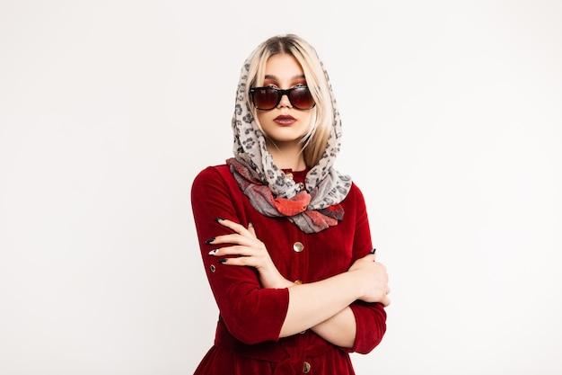 Mulher jovem e atraente na moda em óculos de sol da moda em um vestido elegante cor de vinho com lenço de leopardo vintage na cabeça posando dentro de casa.
