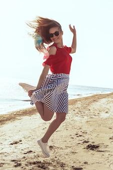 Mulher jovem e atraente na praia do oceano ao pôr do sol