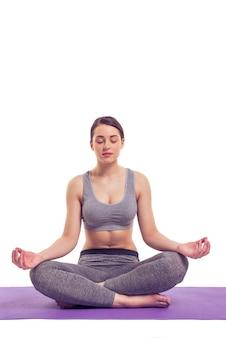 Mulher jovem e atraente no desgaste dos esportes está meditando.