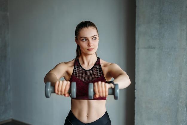 Mulher jovem e atraente no esporte vestindo uma garota sorridente em trens com halteres no estúdio