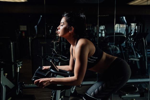 Mulher jovem e atraente no ginásio andando na bicicleta de fiação.