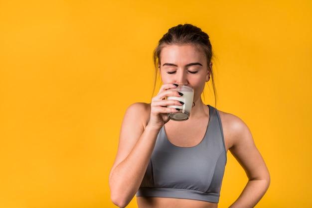 Mulher jovem e atraente no sportswear bebendo leite